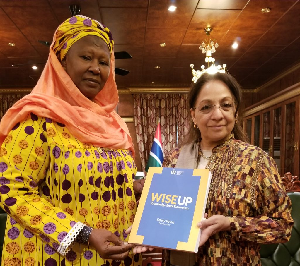 "Daisy Khan, the Executive Director of WISE, poses with the Vice President of the Gambia, Fatoumata Jallow Tambajang, both holding up a copy of ""WISE UP: Knowledge Ends Extremism"""