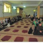 Afghan Women Sitting in a Mosque with red carpets underneath them