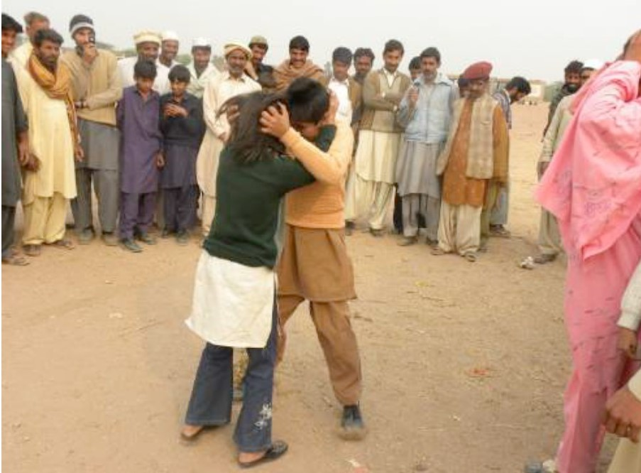 Two Pakistani boys mimic a domestic violence dispute for a street theatre performance for WISE and Bedari