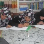 Afghan women in hijabs intently writing on pieces of paper