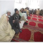 Afghan men sitting in a masjid with red prayer mats