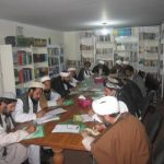 Afghan imams gathered at a table, writing on pieces of paper