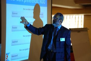 A Pakistani man presenting in front of a projector screen